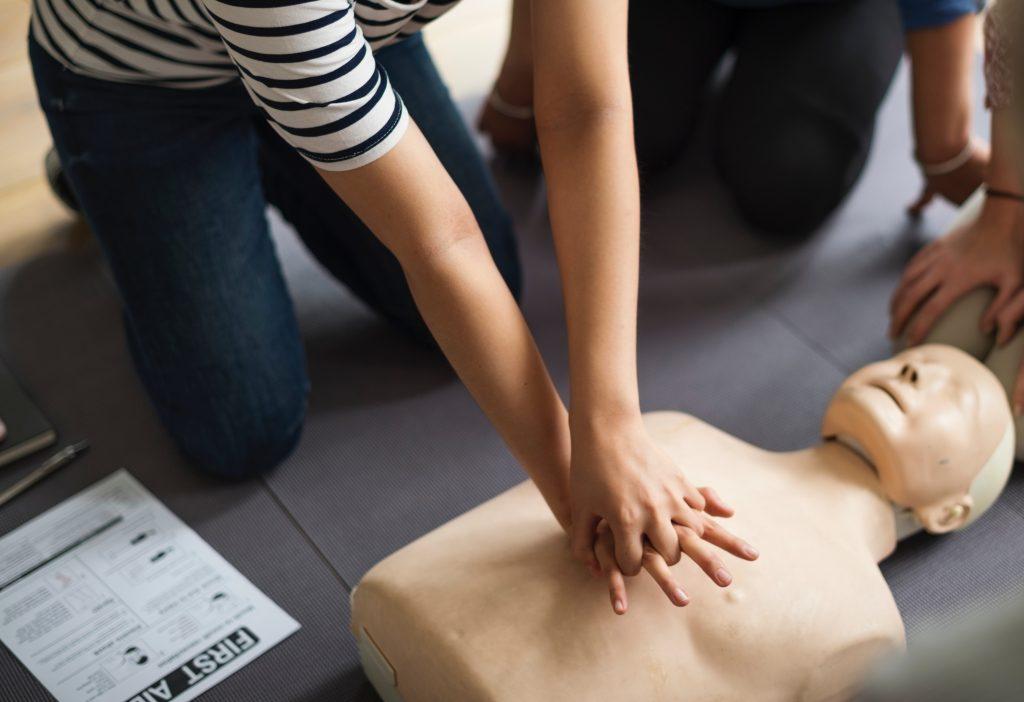 en femme s'entrainant aux gestes de premiers secours sur un mannequin de secourisme