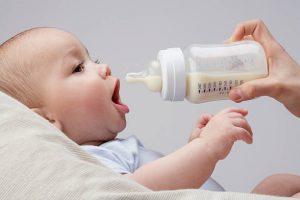 Bébé la bouche grande ouverte en train d'être nourri au biberon