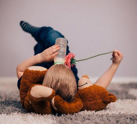 Enfant de dos allongé par terre sur son nounours et buvant un biberon de lait seul