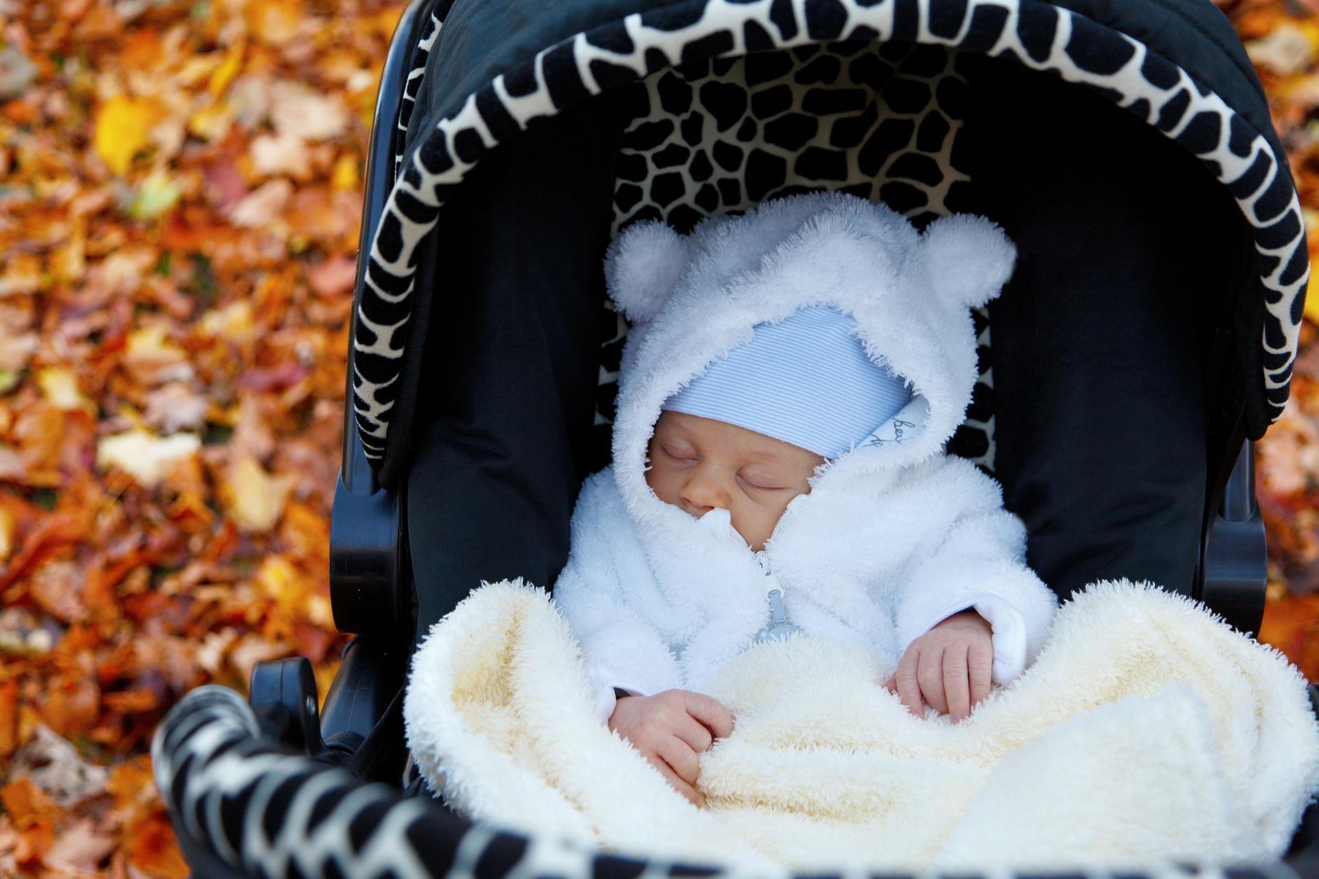 un bébé avec un manteau blanc qui dort dans une poussette