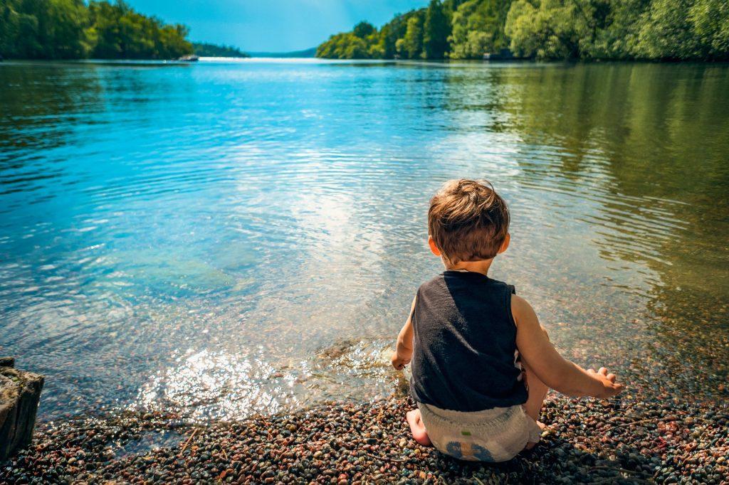 un petit garçon au bord d'un lac