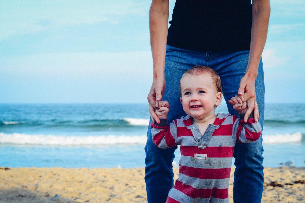 Un bébé sur la plage en train de marcher avec son père
