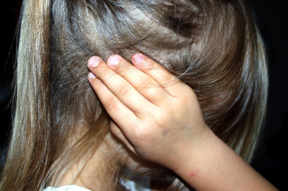 Petite fille qui se bouche les oreilles à cause du bruit