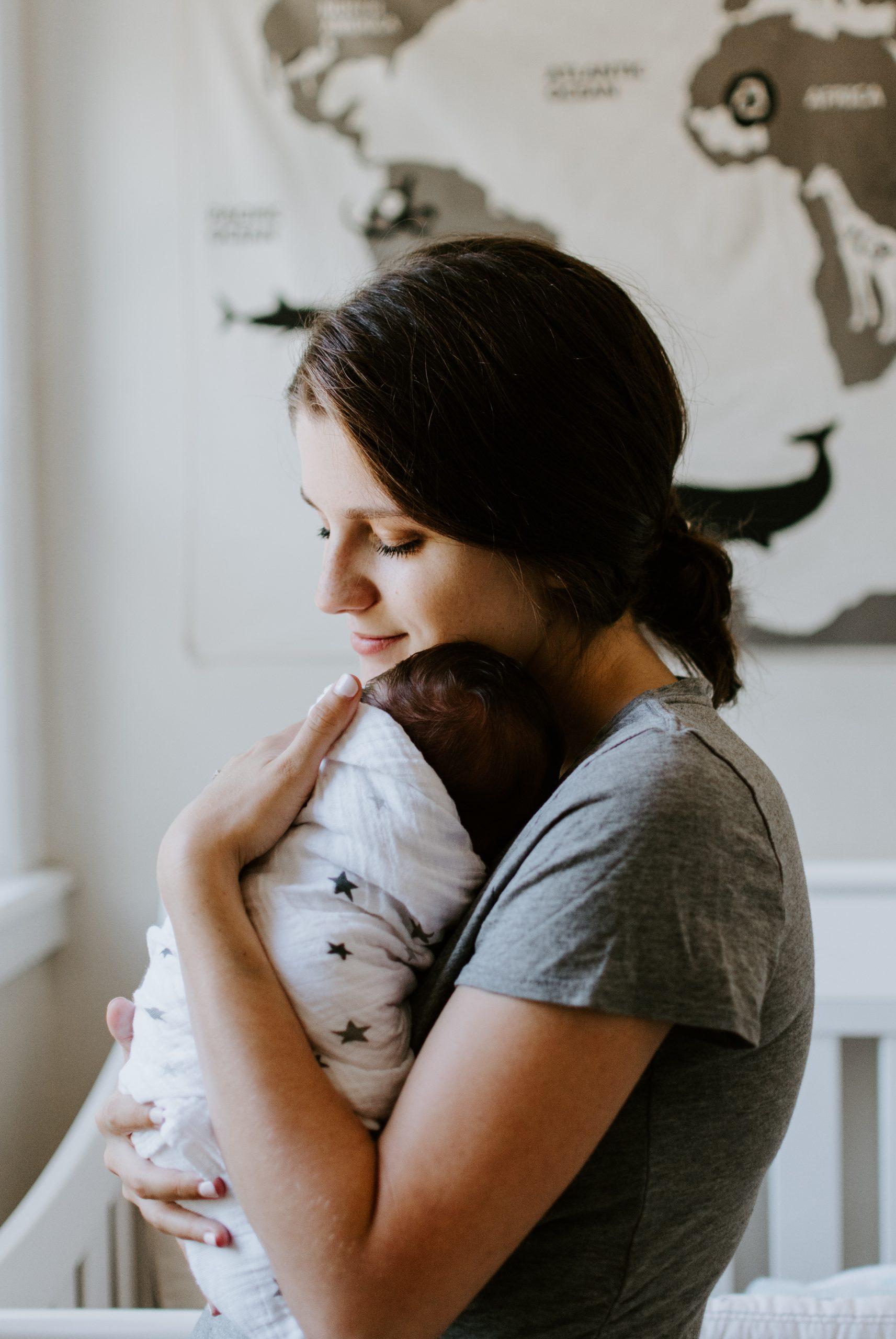 maman avec son bébé dans les bras dans un lange