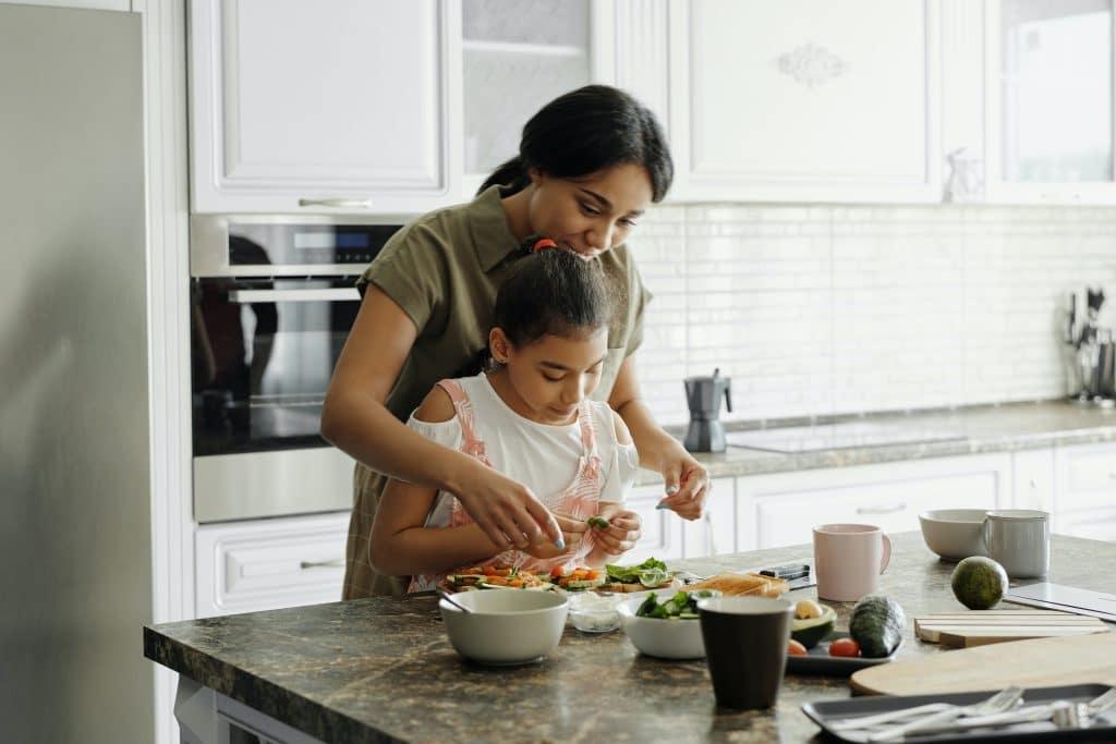 Maman qui cuisine du poisson avec son enfant